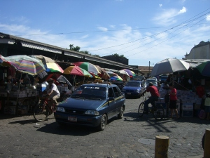 Bikes and cars share a busy street by the San Juan market