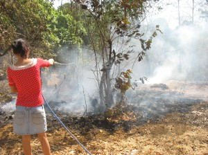 Judy spraying the ashes from the fire.  Flames continued appearing for over an hour.