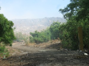 The entrance to the city dump.  The haze covering the mountain is from burning.