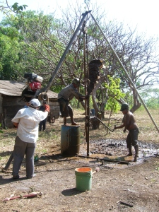 Water is the medium to extract soil from the well.  The motor assists Nelson in raising the tube with the drill bit, and when he let the rope slack the hollow tube drops, spraying out mud.  Santo then uses the attached handle to turn the pipe 90 degrees, and the process is repeated.