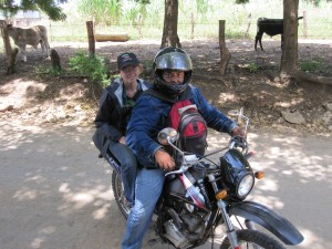 This is how to travel on the rough dirt back roads.  Can you see the mango plants I'm holding onto as well?!